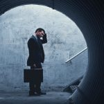 Desparate Businessman Standing and holding his head in a dark tunnel. With room for your text